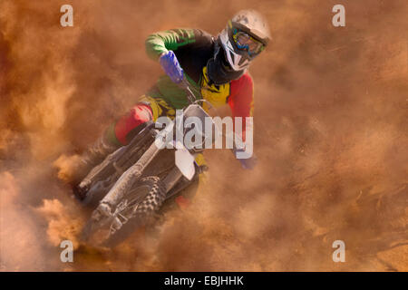 Young male motocross rider racing in dust - Stock Photo
