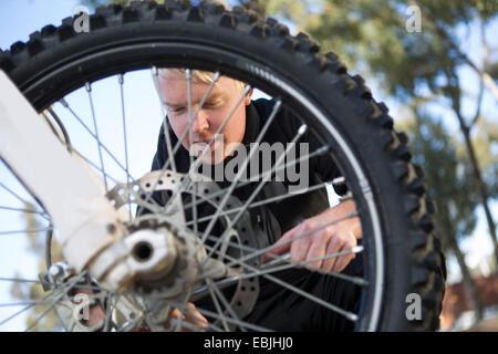 Young male motocross racer adjusting motorcycle wheel in forest - Stock Photo