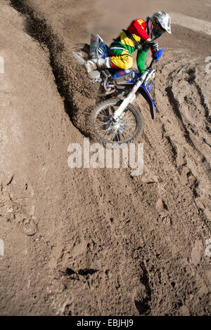 Young male motocross rider racing down mud hill - Stock Photo