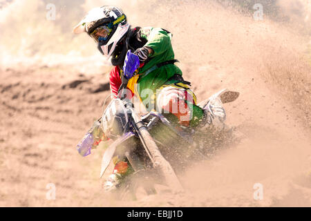Young male motocross rider racing and leaning into mud track - Stock Photo