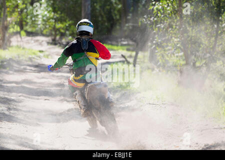 Rear view of young male motocross rider racing on forest track - Stock Photo