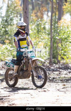 Young male motocross racer standing whilst riding through forest - Stock Photo