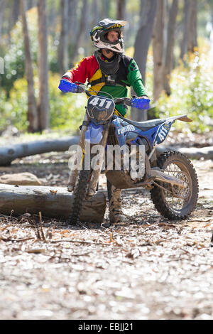 Young male motocross racer standing in forest - Stock Photo