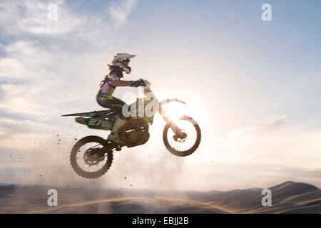 Silhouetted young male motocross racer jumping over mud track - Stock Photo