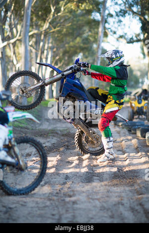 Young male motocross racer holding up motorcycle on forest track - Stock Photo