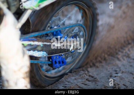 Close up of motocross motorcycle wheel spinning in mud - Stock Photo