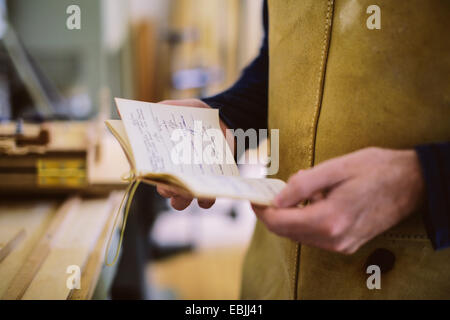 Close up of mid adult craftsman holding notebook in organ workshop - Stock Photo