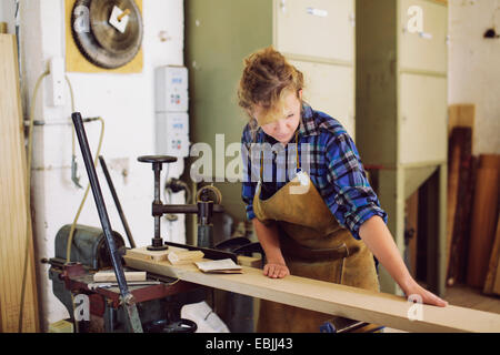 Young craftswoman checking wood in pipe organ workshop - Stock Photo