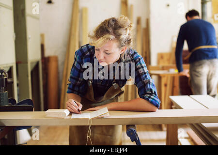 Young craftswoman making notes in pipe organ workshop - Stock Photo