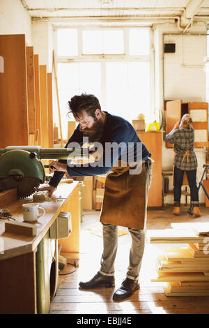 Mid adult craftsman using machinery in organ workshop - Stock Photo
