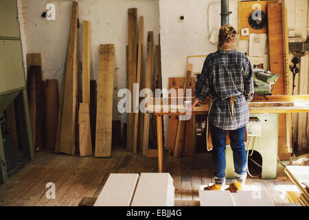 Young craftswoman at workbench in pipe organ workshop - Stock Photo