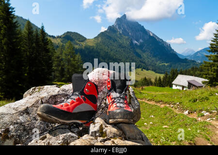 red hiking boots on a hike in the mountains, Austria - Stock Photo