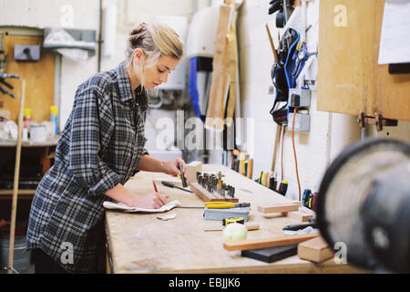 Young craftswoman making notes at workbench in pipe organ workshop - Stock Photo