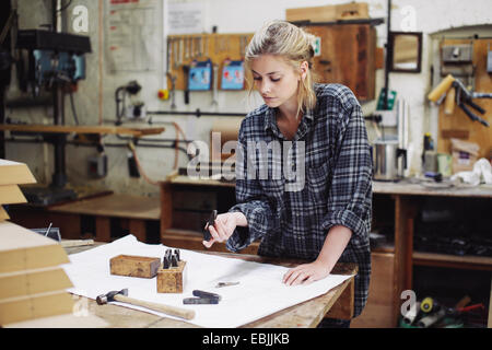Young craftswoman checking components on workbench in pipe organ workshop - Stock Photo
