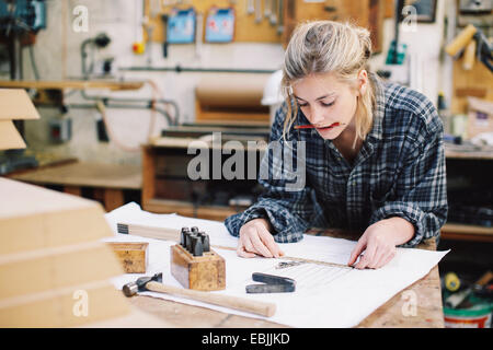 Young craftswoman measuring blueprint on workbench in pipe organ workshop - Stock Photo