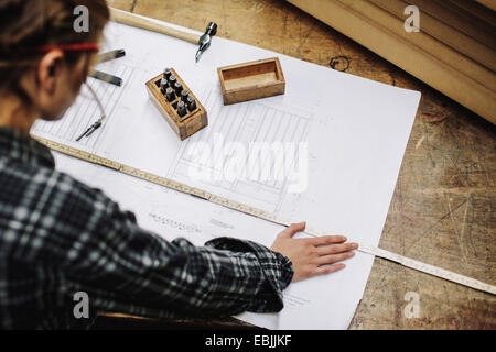 Young craftswoman measuring blueprint in pipe organ workshop - Stock Photo