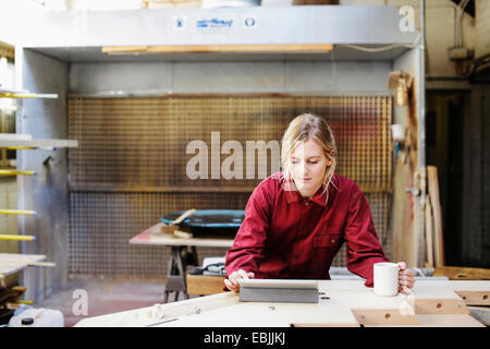 Young craftswoman using digital tablet in pipe organ workshop - Stock Photo