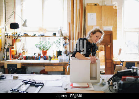 Young craftswoman checking component in pipe organ workshop - Stock Photo