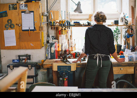 Rear view of young craftswoman at workbench in pipe organ workshop - Stock Photo