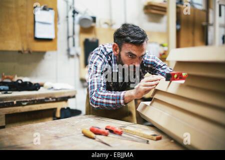 Mature craftsman using spirit level in pipe organ workshop - Stock Photo