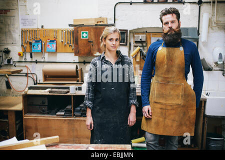 Portrait of craftsman and woman in organ workshop - Stock Photo