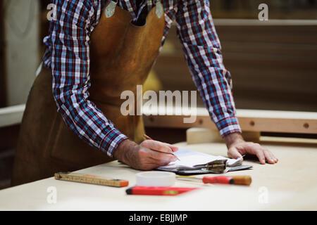 Cropped shot of mature craftsman making notes in organ workshop - Stock Photo