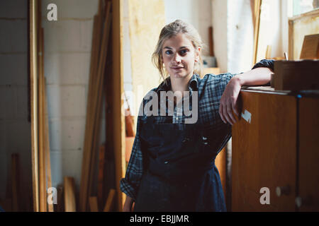 Portrait of young craftswoman leaning on cupboard in organ workshop - Stock Photo