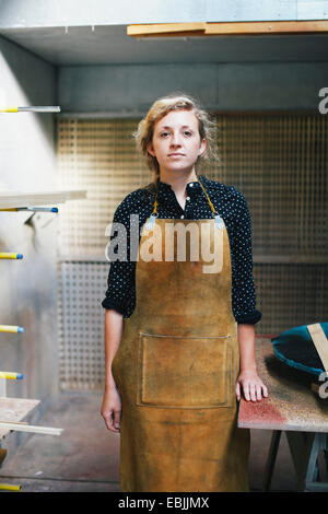 Portrait of young craftswoman in organ workshop - Stock Photo