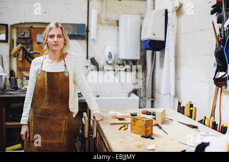Portrait of young craftswoman leaning on workbench in organ workshop - Stock Photo