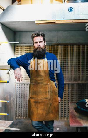 Portrait of mid adult craftsman leaning on shelf in organ workshop - Stock Photo