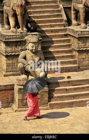 woman with an umbrella serving as a sunshade crossing the Bhaktapur Durbar Square at the royal palace, Nepal, Bhaktapur - Stock Photo