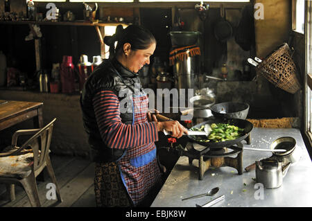 woman cooking in the kitchen of a lodge at the Annapurna massif, Nepal - Stock Photo