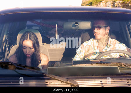 Young couple in car on road trip - Stock Photo