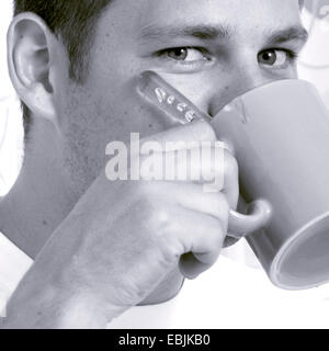 young man drinking out of a coffee cup - Stock Photo