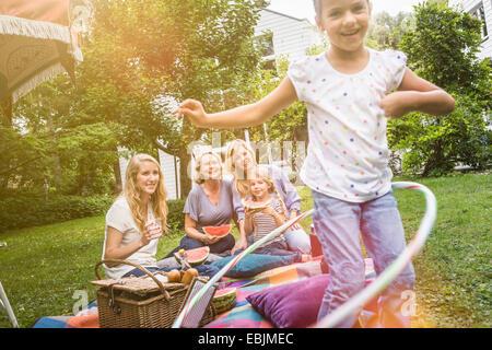 Girl playing with hula hoop at family picnic - Stock Photo