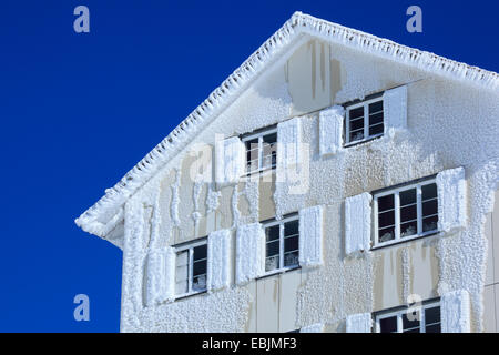 snow-covered  facade of a residental house in front of a clear blue sky, Switzerland - Stock Photo
