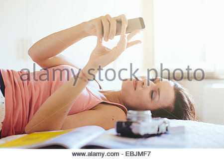 Mid adult woman lying on bed reading messages on smartphone - Stock Photo