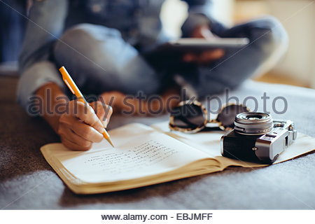 Cropped shot of mid adult woman sitting on bed writing in notebook - Stock Photo