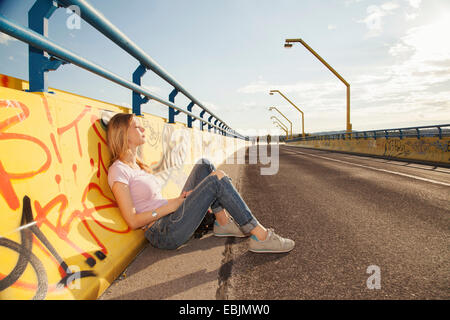 Young woman sitting leaning against graffiti wall on bridge in sunlight - Stock Photo
