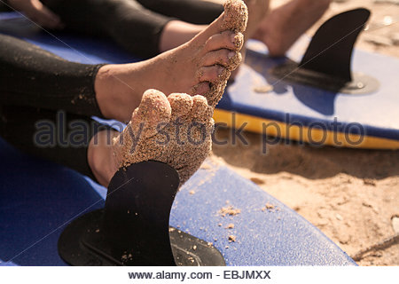 Boy's feet on surfboard, close up - Stock Photo