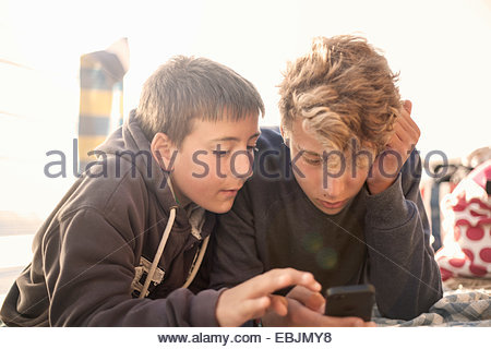 Two boys using smartphone - Stock Photo