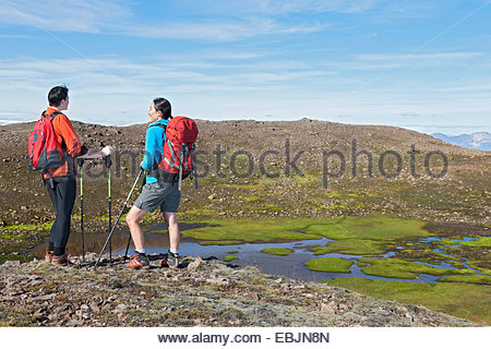Hikers looking out over Dyrfjoll Mountain range, East Iceland, Iceland - Stock Photo