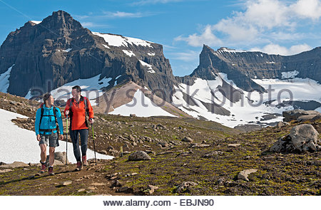 Hikers hiking at Dyrfjoll Mountain range, East Iceland, Iceland - Stock Photo