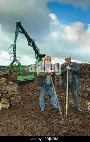 two peat cutters between stacks of bales of peat and the excavator for loading the moor railway, Germany, Lower - Stock Photo