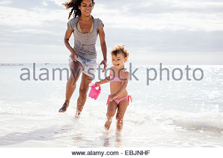 Mother and toddler daughter running with toy watering can on beach, Tuscany, Italy - Stock Photo