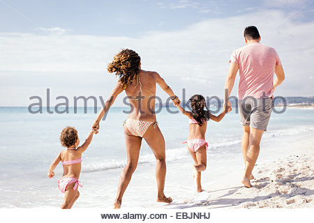 Couple and two girls running and holding hands on beach, Tuscany, Italy - Stock Photo