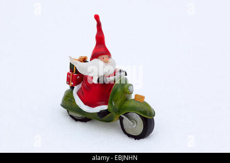 Santa claus on motor bike, ceramic figure in snow, Switzerland - Stock Photo