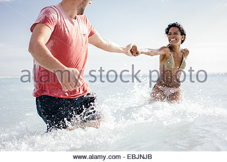 Couple wading and holding hands in sea, Tuscany, Italy - Stock Photo