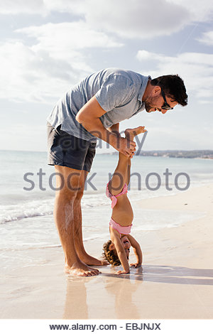 Female toddler doing handstand helped by father at beach, Tuscany, Italy - Stock Photo