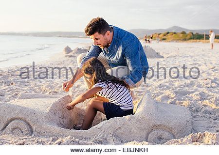 Girl and father with sophisticated car sandcastle on beach, Tuscany, Italy - Stock Photo